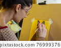 The artist draws a drawing on an easel, side view, close-up 76999376