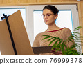 Portrait of an artist at work, a girl draws a drawing on an easel by the window 76999378