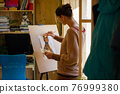 The artist paints a drawing of a cat with acrylic paints on an easel, in a small workshop by the window 76999380