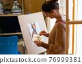 The artist mixes paints on a palette painting at home by the window 76999381