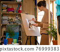 Girl artist draws on an easel at home 76999383