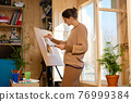 Girl artist draws on an easel at home, molubert stands at the window 76999384