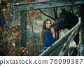 A beautiful girl in a blue stole stands next to a horse on the background of wooden buildings 76999387