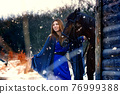 Beautiful girl in a blue stole stands next to a horse near wooden buildings on a snowy winter day 76999388