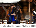 Beautiful girl in a blue stole hugs a horse near wooden buildings on a winter day 76999389