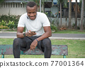Young man exercise and listen music in park. 77001364