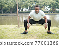 Young man exercise and listen music in park. 77001369
