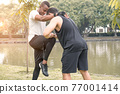 Two muscular men exercising together by a river 77001414