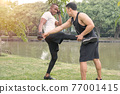Two muscular men exercising together by a river 77001415