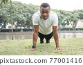 African American sportsman pushups on green grass 77001416