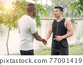 Man athlete and trainer relax talk after training 77001419