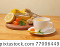 Ginger tea with mint and lemon. Healthy and hot drink. Liquid honey in honey-jar. White cup on wooden background. Selective focus. 77006449