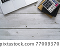 Laptop, calculator and notebook on white wood table with copy space. Top view of business financial concept 77009370