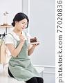 주방에서 케익을 먹는 여성 77020836