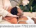 Young healer working woith a dark-skinned patient in ayurvedic salon 77021039