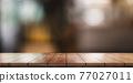 Empty wooden table top with lights bokeh on blur restaurant background. 77027011