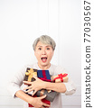 Senior asian woman holding mount of gift boxes, enjoying many best presents. 77030567