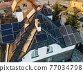 Aerial view of solar photovoltaic panels on a house roof 77034798