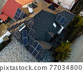 Aerial view of solar photovoltaic panels on a house roof 77034800