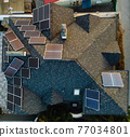 Aerial view of solar photovoltaic panels on a house roof 77034801