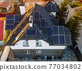 Aerial view of solar photovoltaic panels on a house roof 77034802