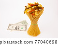italian pasta with a dollar bill on a white background. flour products and food in cooking 77040698