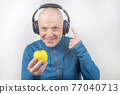 happy man wearing portable full-size headphones listens to music using an apple player. 77040713