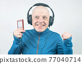 happy man in portable full-size headphones listens to music using a digital player. 77040714