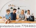 Happy family preparing snacks in air fryer 77044663