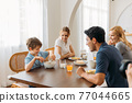 Family looking at boy pouring milk in cereals 77044665