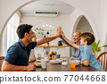 Family giving high-five during breakfast 77044668