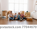 Family with cardboard boxes waving hand 77044670