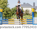 Teen girl jumping horse on her show jumping course 77052433