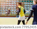 Young field hockey girl player with stick at pitch 77052435