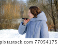 Lady in blue coat is sending audio voice message explaining something on smart phone at outdoor talking to mobile assistant. Girl using smartphone voice recognition and dictation 77054175
