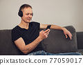 The man in headphones and with a smartphone sits on the couch. 77059017