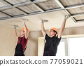 Workers are attaching plasterboardto the ceiling. 77059021