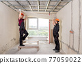 Workers are lifting drywall to attach to the ceiling. 77059022