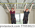 Installation of drywall. Workers are measuring. 77059023