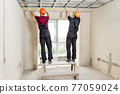Installation of drywall. Workers are measuring. 77059024