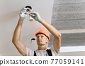 The electrician is installing LED spotlights on the ceiling. 77059141