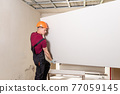 The worker is holding plasterboard for mounting to the ceiling. 77059145
