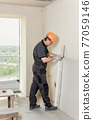 Installation of drywall. The worker is cutting plasterboard. 77059146