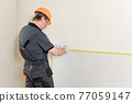 Installation of drywall. The worker is measured to cut plasterboard. 77059147