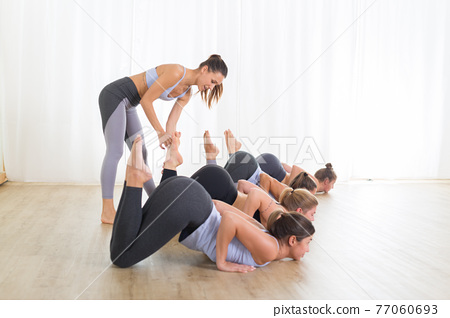 Group of young sporty sexy women in yoga studio, practicing yoga lesson with instructor, forming a line in front bent puppy dog asana pose. Healthy active lifestyle, working out indoors in gym 77060693