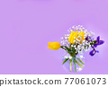 Beautiful bouquet of yellow tulips, iris and baby's-breath in round glass bowl on violet background. 77061073