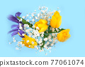 Beautiful bouquet of yellow tulips, iris and baby's-breath on blue background. 77061074