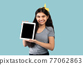 Cute Indian adolescent girl holding tablet pc with blank screen on blue background, space for app or website design 77062863