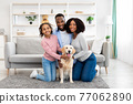 Young black family hugging dog posing at home 77062890