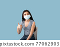 Vaccinated teen girl in face mask showing plaster bandage on her arm after getting covid-19 vaccine injection 77062903